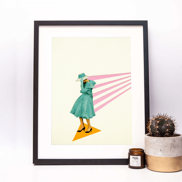 framed print of a lady in a green coat holding onto her had as she gets blown in the wind